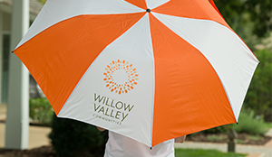 Willow Valley Communities orange and white umbrella with logo on it